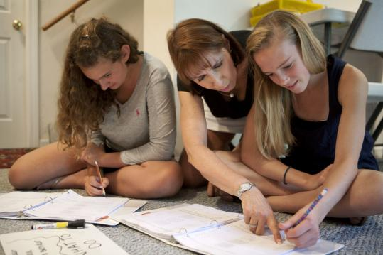 Summer Math for All founder Christine Moynihan helps 14-year-old Lisa Peters (left) and Kristina Baldwin, 13, with math activities in Holliston.