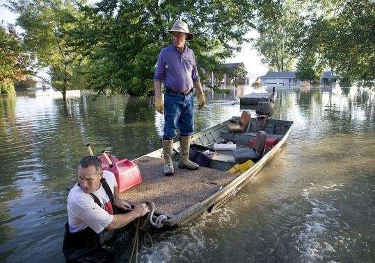 Pat Murphy (left) pulled Rob Anderson to their homes along the Missouri River last week in flooded Dakota Dunes, S.D.