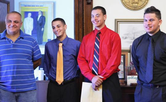 Coach Mike Petrides and players (from left) Gilbert Simas, Jonathan Pires, and Emmanuel Gonzalez at Medford City Hall.