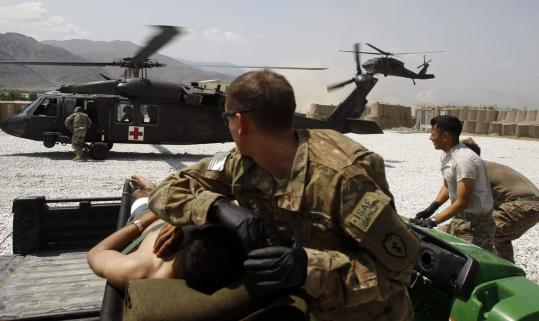 A US army medic from 2-35 Infantry Battalion protects an injured Afghan national army soldier in Kunar province, Afghanistan, last month. Army medics often have to go through extensive retraining to be eligible for similar jobs in the civilian world.
