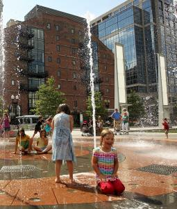 Children cool off in the Greenway's sprinkler park last month.