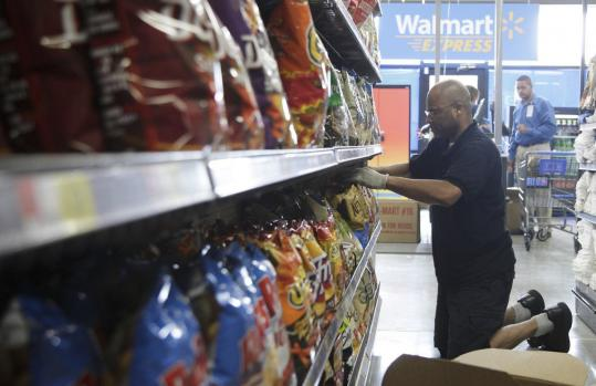 A worker stocked shelves at a Wal-Mart store in Chicago. Wal-Mart is restoring several items in a bid to lure shoppers.