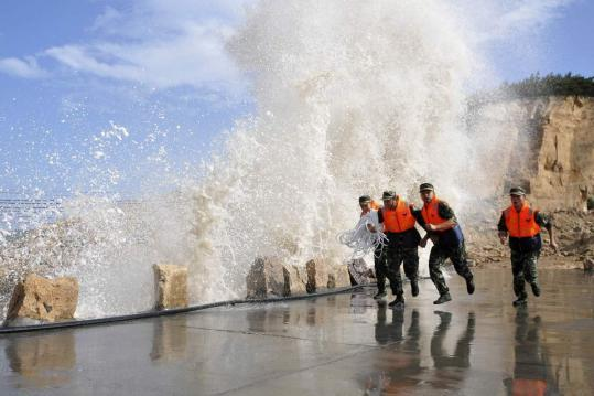 As waves pounded the coast in Zhejiang Province yesterday, soldiers began making preparations for Typhoon Muifa.