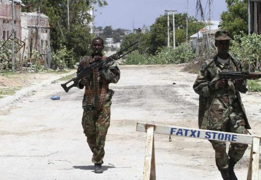 Somali government soldiers patrolled a main road near the deserted main Bakara market in the capital Mogadishu yesterday. Islamist fighters withdrew from the city but an Al Shabab spokesman says the group will launch a counterattack.