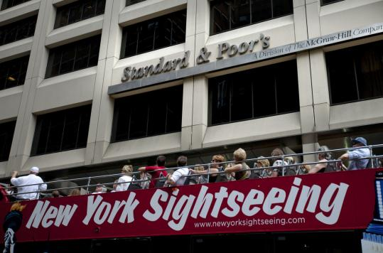 Tourists in New York were driven past Standard & Poor's, which lowered the US credit rating to AA+. S&P cited the nation's insufficient commitment to reducing budget deficits.