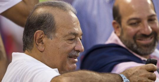 Carlos Slim, the richest man in the world, checks his cellphone while checking out the game from Red Sox owner John Henry's seats.