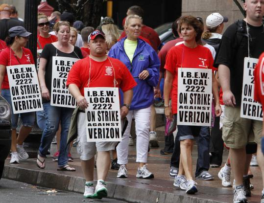 Verizon workers picket outside of the company's New England headquarters in Boston Sunday.