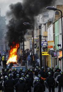 Police in riot gear blocked a road late yesterday near a burning car in the London neighborhood of Hackney, where bands of hooded youths hurled objects at police.