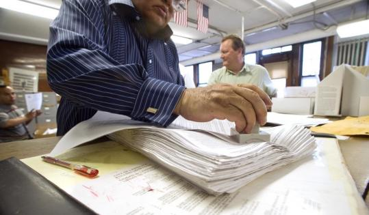 A Lawrence Election Department employee processed signed recall petitions yesterday.