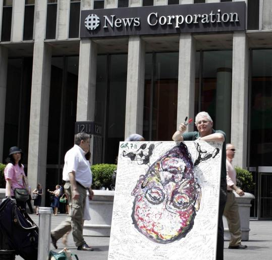 "Artist Geoffrey Raymond was displaying his painting ""Inverted Murdoch'' in front of News Corp.'s building in New York last week."