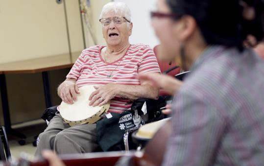 Mary DiCenso sings along during a drumming circle at Hebrew Rehabilitation Center at NewBridge on the Charles.