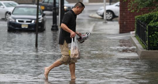 A deliveryman waded through a Hoboken, N.J., street Sunday. Seabrook Farms, N.J., had nearly 11 inches of rain, while New York's John F. Kennedy International Airport got nearly 8 inches.