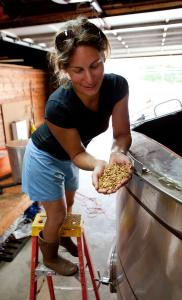 Andrea Stanley, co-owner (with her husband, Christian) and maltster at Valley Malt in Hadley, holds steeping barley, and, grown in her field, heirloom barley.