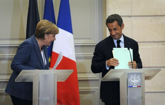 German Chancellor Angela Merkel and French President Nicolas Sarkozy at a news conference yesterday in Paris. They called for all eurozone nations to require balanced budgets