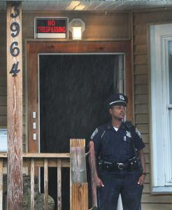 Boston Police kept watch outside the Roslindale three-decker where a teenager, his mother, and her friend were shot last week.