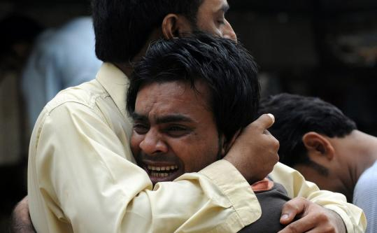 A Pakistani man comforted a mourner yesterday after the killing of a man outside a hospital in Karachi, where violence has flared. The gangs carrying out killings are allegedly affiliated with the city's main political parties.