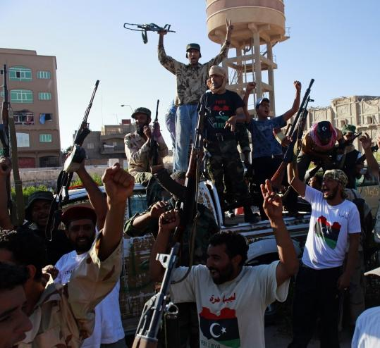 Rebels celebrated yesterday after taking control of Sabratha, Libya, one of several coastal town seized by the opposition, further cutting off Moammar Khadafy and the capital from supplies.
