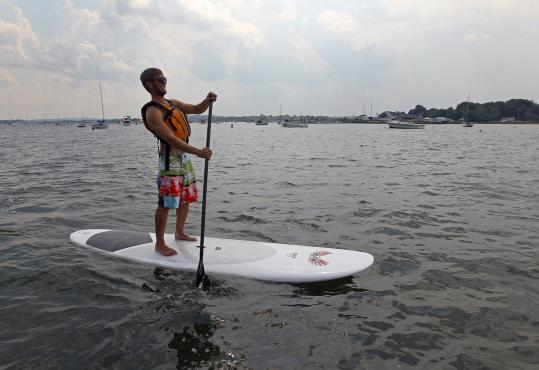 Michael Emery of Somerville did some stand-up paddleboarding in Savin Hill Cove near the University of Massachusetts Boston.