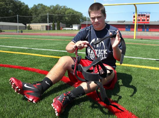 Natick High junior Jack Lowell, who badly injured his knee last year, puts on the brace that he will wear this season.
