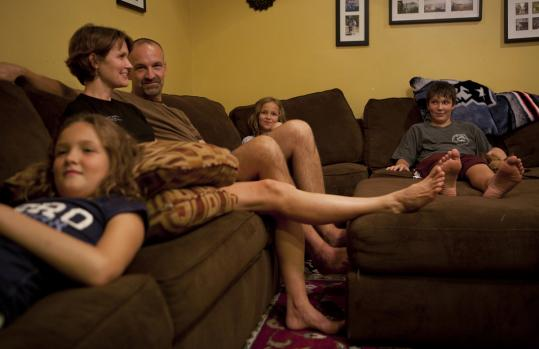 Anita and Michael Lotti watch a movie in their Holliston home with their children, Meghan, 11 (left), Julianna, 8, and Jay, 14.