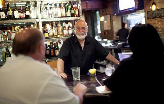 Longtime bartender Reggie St. Paul, 70, talks to friends Lonnie and Marcia Hillson; he's known Lonnie for 60 years.
