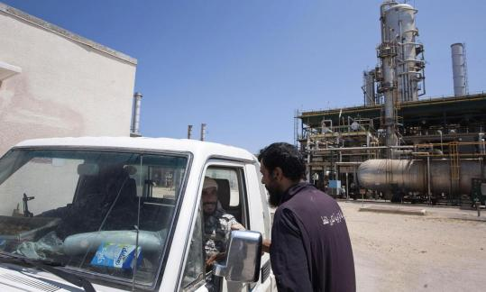 A worker chatted Friday with rebels in a vehicle who were patrolling an oil refinery controlled by anti-Khadafy forces. Before the rebellion, Libya exported 1.3 million barrels of oil a day.