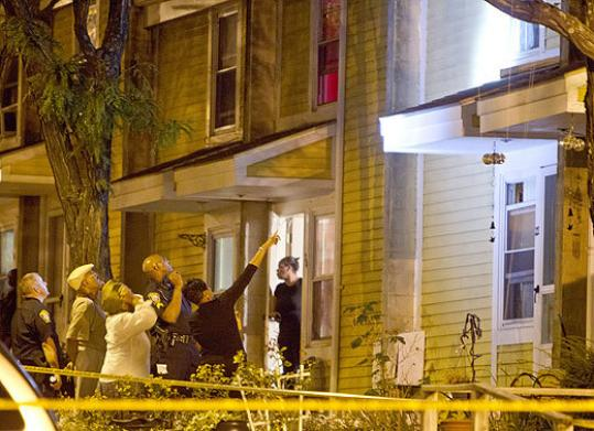 Boston police and residents looked to the second story of a house in Kensington Park, which was the scene of a double shooting last night in Roxbury.