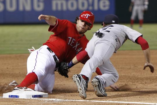 The Rangers' Ian Kinsler slides into third base ahead of the tag applied by Boston's Jed Lowrie in the third inning.