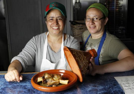At Moroccan Hospitality Restaurant, Amina Ghalley McTursh (left) and Nouzha Ghalley open a tagine holding lamb with prunes.