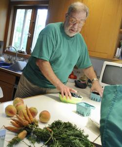 Bob Blanchard sorts the vegetables from his CSA.