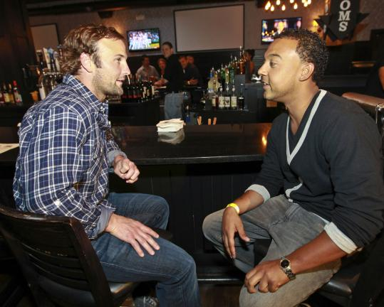 Wes Welker (left) chats with Anthony Marinez at the Tavern in the Square in Allston.