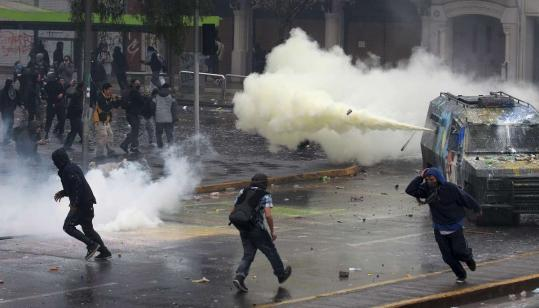 Demonstrators and riot police clashed in Santiago yesterday during a two-day strike against the government.