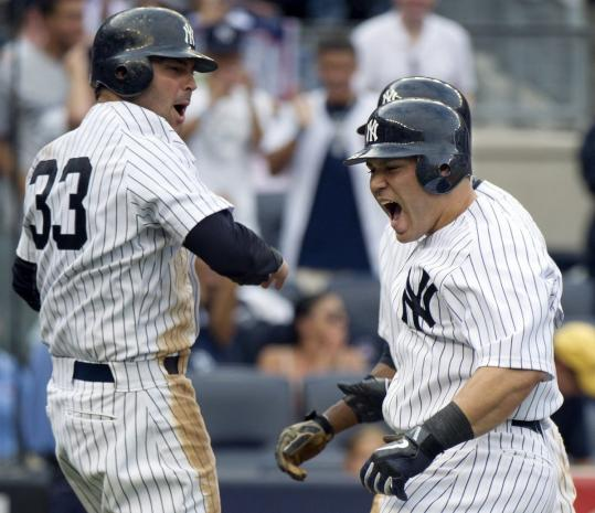 Nick Swisher (left) helps Russell Martin celebrate Martin's grand slam in the sixth - the second of three slams by the Yankees.