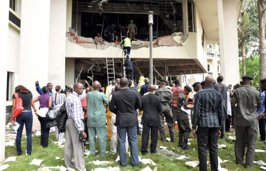 Rescuers worked yesterday in the debris of the UN headquarters in Abuja, Nigeria. Below, an injured man was rescued.