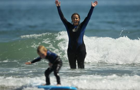 Sandy Kirby of Hampton, N.H., cheered as her surfing son, 4-year-old Jonah Kirby, rode a small wave off North Beach. With Hurricane Irene still far south of the region, the beach was crowded yesterday.