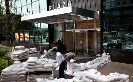 Workers at a residential building in the financial district of Manhattan stacked sandbags in anticipation of flood waters yesterday.