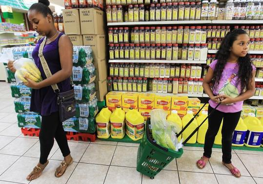 Luisanna Diaz, 13, and Yiskania Diaz, 9, shop with their mother at La Fruteria in Lawrence, where owner Alberto Santana is hearing more requests for healthy foods.