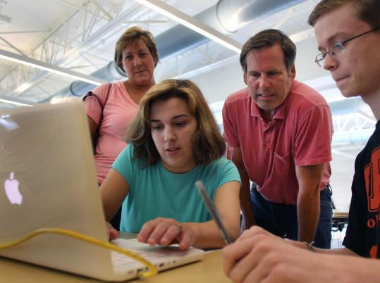 Beverly High's Casey Hogan, 15, logs on to a MacBook as her parents, Patty and Dan, and tech intern Connor Lafata look on.