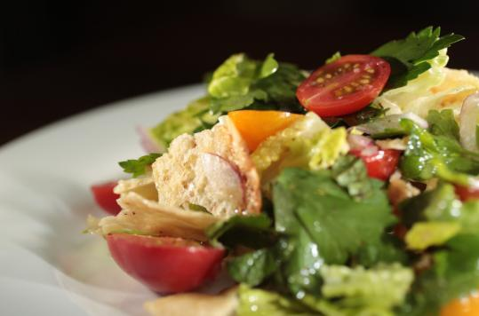 A fattoush salad includes toasted pita, lettuce, tomatoes, cucumber, parsley, red onion, and mint.