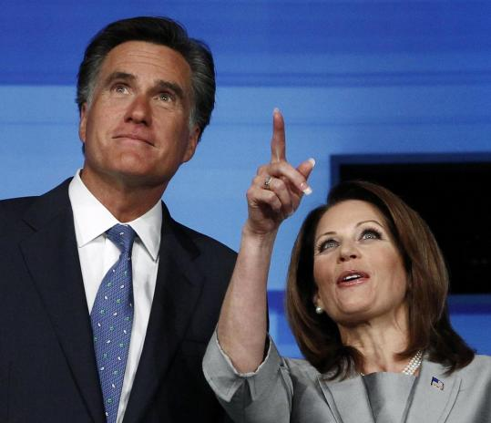 Mitt Romney, a Mormon, speaks with conservative Christian Michele Bachmann at a debate in Iowa earlier this month.