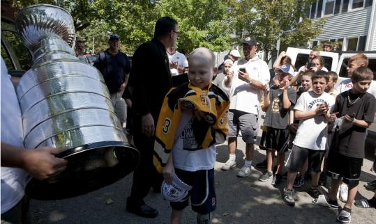 Tim Burke (top and above right, with his friend Chris Gallagher) with the Stanley Cup at his home in South Boston.