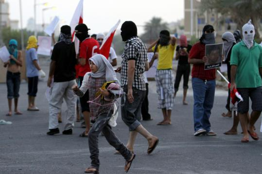 A girl ran past protesters yesterday in Sitra, Bahrain, where a teen died earlier in the day.