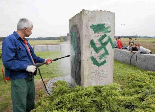A man cleaned a defaced monument that marks the site of the mass killings of Jews in Jedwabne, Poland, during World War II.
