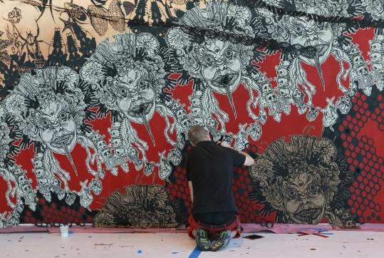 A crew member works on &#8220;Anthropocene Extinction,&#8217;&#8217; an art installation by Brooklyn street artist Swoon (right) at the Institute of Contemporary Art.