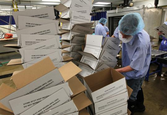 Workers sorted boxes inside a lobster-processing plant owned by Linda Bean, who got into the lobster business several years ago by purchasing a wharf near her home in Port Clyde.