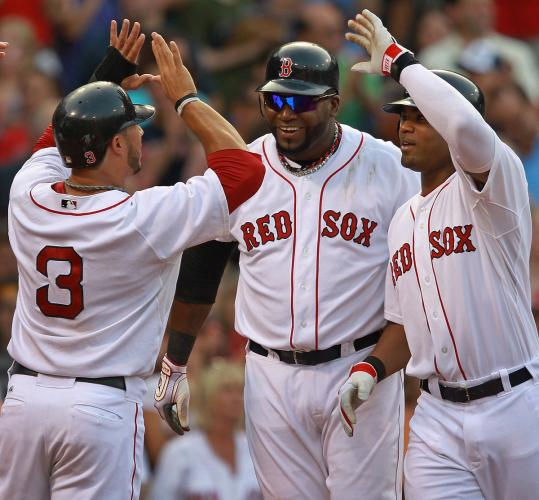 Carl Crawford (right) is greeted at the plate by Mike Aviles (3) and David Ortiz after belting a grand slam in the fourth.