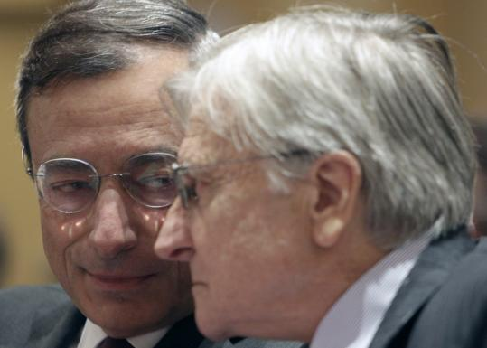 European Central Bank head Jean-Claude Trichet (right) with his successor Mario Draghi at a debt-crisis conference yesterday in Paris.