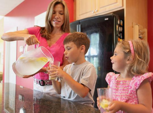 "Colleen Lawton of Newburyport pours water with lemon for Steven, 6, and Brooke, 3. ""They would drink juice if it were up to them,'' Lawton says."