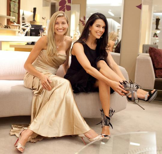 Lindsay Buchholz (left) and Linda Pizzuti Henry try on shoes in preparation for the fashion benefit on Sept. 15.