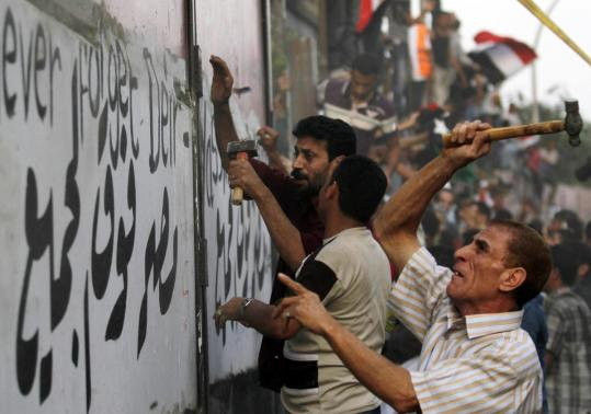 Protesters tore down a wall at the Israeli Embassy in Cairo yesterday. The ambassador and others were evacuated.